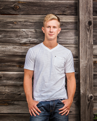A Young man with blond hair poses against a rustic barn in his Senior Portrait