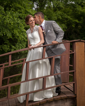 A Bride and Groom kissing on a bridge