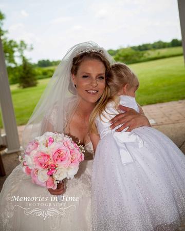 A Summer bride gives her flower girl a re-assuring hug.