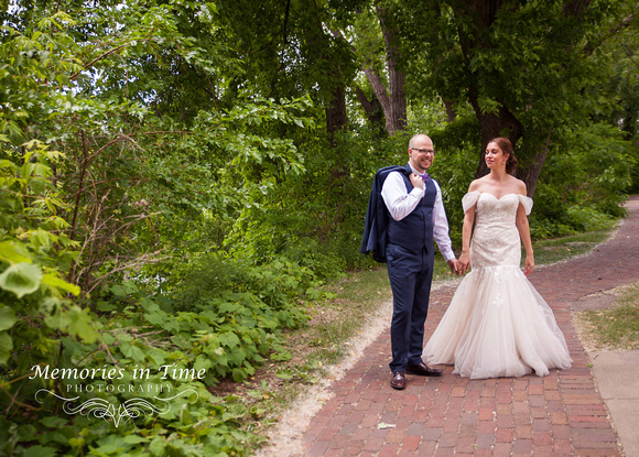 A newly married couple walking along St. Anthony Falls, Minneapolis, MN
