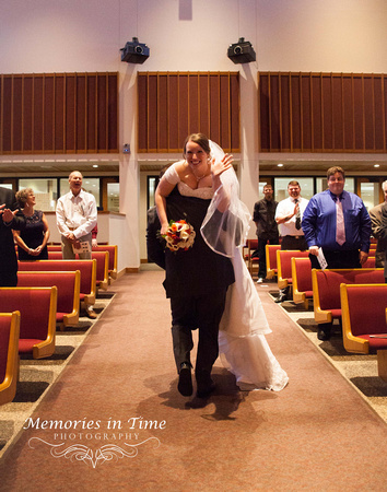 The Groom carrying his bride over his shoulder and out of the church