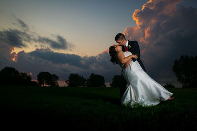A wedding couple kiss surrounded by the colors of a sunset