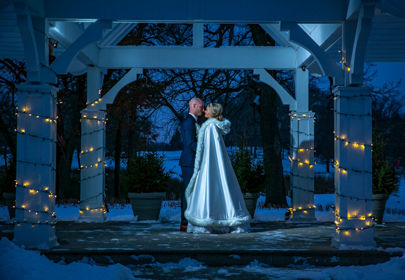 A bride and groom shares a romantic kiss surrounded by show and glittery lights