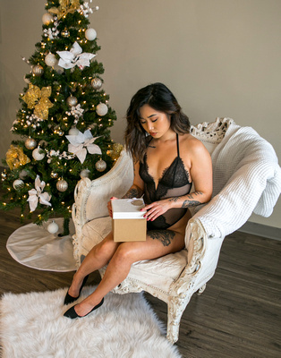 A woman in black lingerie poses near a Christmas tree while she opens presents.